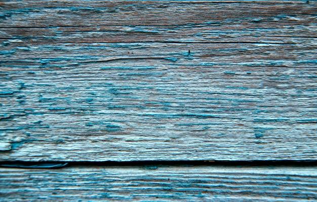 Tábuas de madeira pintadas de azul. superfície áspera e rachada. madeira velha e pintura.