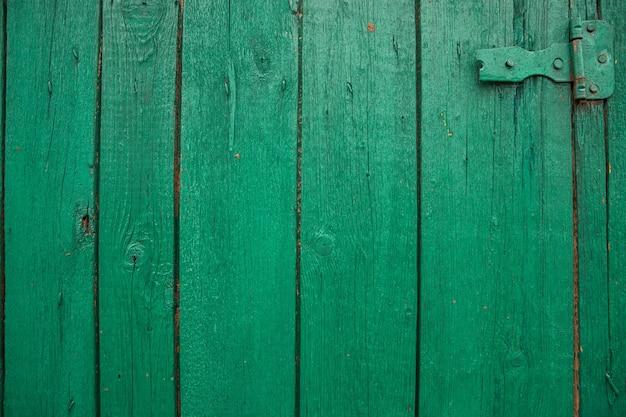 Tábuas de madeira pintadas na cor verde. superfície áspera e rachada. madeira velha e pintura.