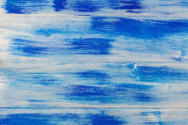 Tábuas de madeira pintadas várias vezes por tintas brancas e azuis