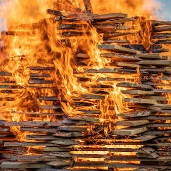 Tábuas de madeira queimam com uma chama laranja grande e flamejante com bruxas tradicionais em chamas