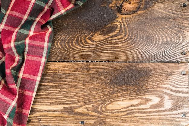 Tábuas de madeira rústicas com toalha de mesa quadriculada vermelha