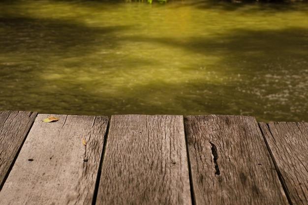 Tabuleiro baixar mesa de madeira na frente da paisagem de verão da água do lago cintilante