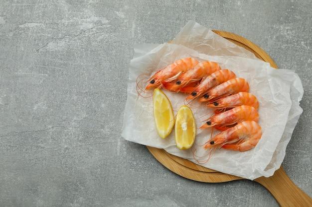 Tabuleiro com camarão e limão no plano de fundo texturizado cinza