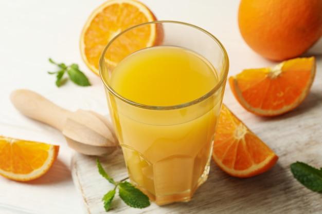 Tabuleiro com copo de suco de laranja, laranja e espremedor em madeira