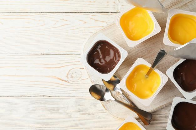 Tabuleiro com copos plásticos de iogurte e colheres em cinza