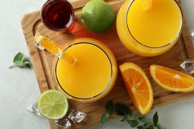 Tabuleiro com coquetéis tequila sunrise na mesa texturizada branca