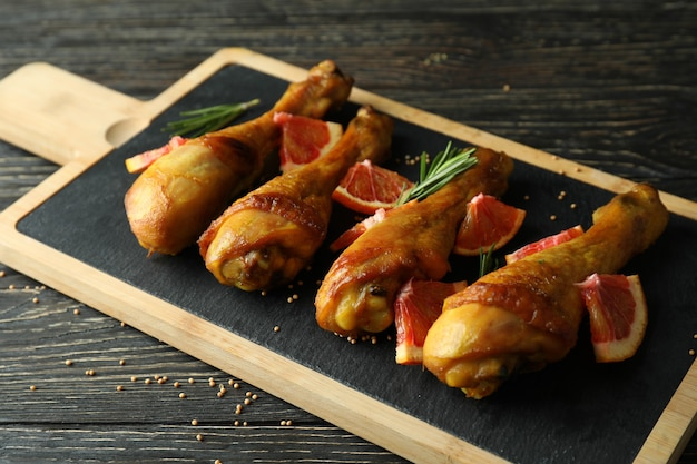 Tabuleiro com coxinhas de frango assado em fundo de madeira