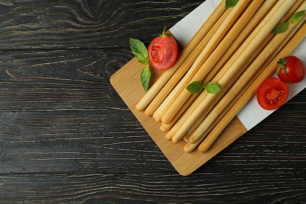 Tabuleiro com grissini breadsticks na mesa de madeira