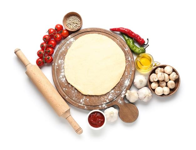 Tabuleiro com ingredientes para pizza na superfície branca