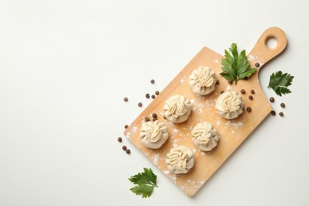 Tabuleiro com khinkali, especiarias e farinha na mesa branca