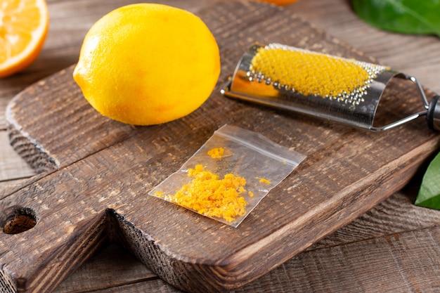 Tabuleiro com limão e raspas na mesa de madeira, closeup