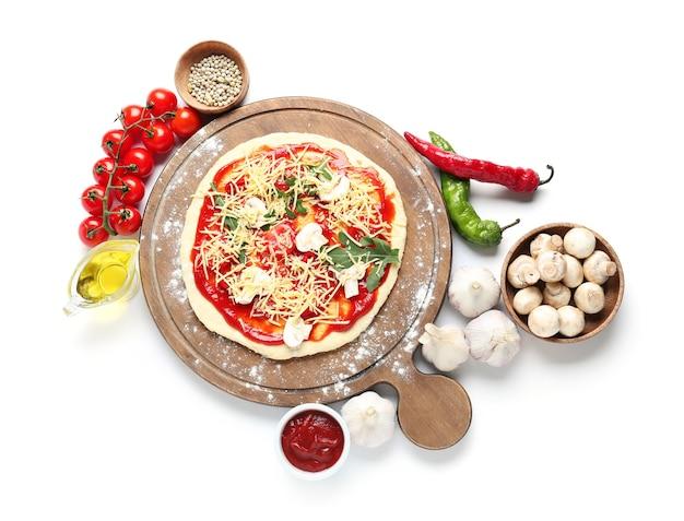 Tabuleiro com pizza crua na superfície branca