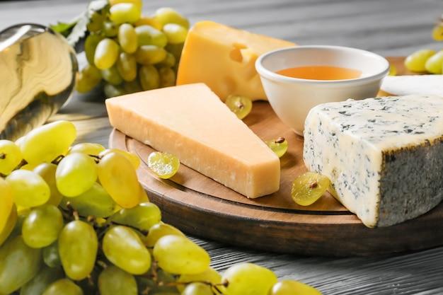 Tabuleiro com queijo e uvas maduras na mesa de madeira