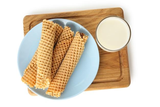 Tabuleiro com rolinhos de wafer com leite condensado e leite isolado no branco