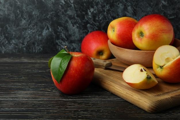 Tabuleiro com saborosas maçãs vermelhas na mesa de madeira