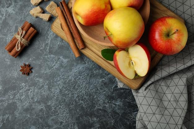 Tabuleiro com saborosas maçãs vermelhas na mesa preta esfumada