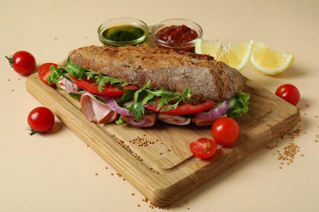 Tabuleiro com sanduíche de ciabatta e ingredientes em fundo bege