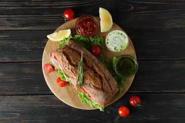 Tabuleiro com sanduíche de ciabatta e ingredientes na mesa de madeira