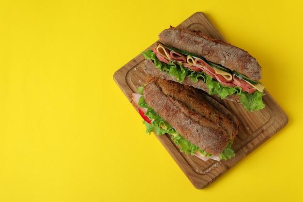 Tabuleiro com sanduíches de ciabatta em fundo amarelo