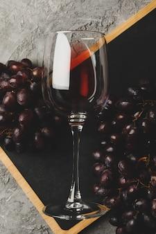 Tabuleiro com uva e copo de vinho no fundo cinza