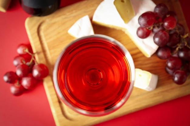 Tabuleiro com vinho, queijo e uva sobre fundo vermelho