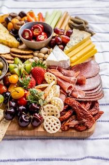 Tabuleiro de charcutaria com charcutaria, fruta fresca e queijos de perto