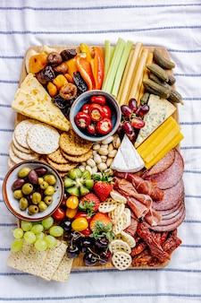 Tabuleiro de charcutaria com charcutaria, frutas frescas e queijos de perto