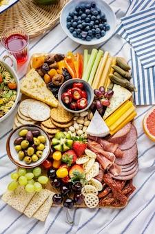 Tabuleiro de charcutaria com charcutaria, frutas frescas e queijos numa toalha de piquenique