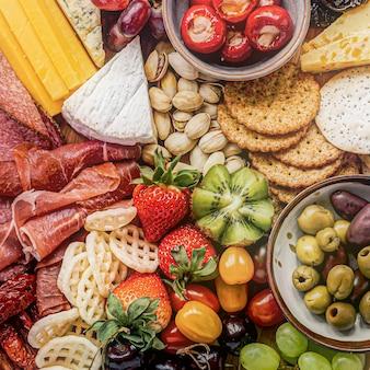 Tabuleiro de charcutaria com charcutaria, frutas frescas e queijos