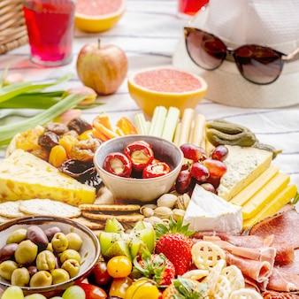 Tabuleiro de charcutaria com frios, frutas frescas e queijos, piquenique de verão