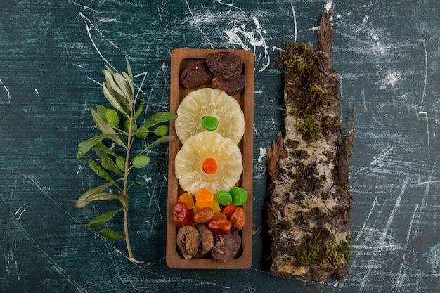 Tabuleiro de frutas secas e gelatinosas com um pedaço de madeira em uma mesa azul