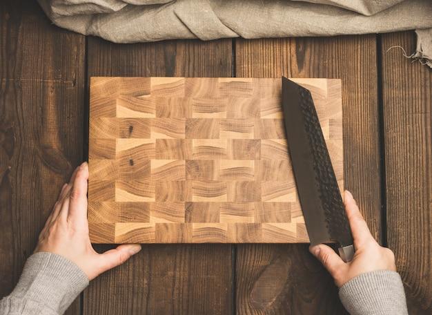 Tabuleiro de madeira retangular vazio e mãos femininas com uma faca, vista superior