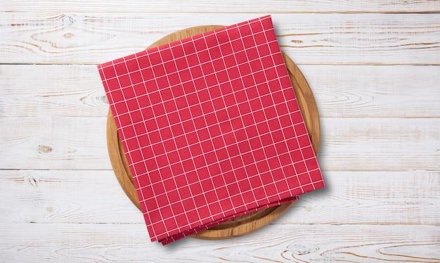 Tabuleiro de pizza vazio e toalha vermelha em deck de madeira branco
