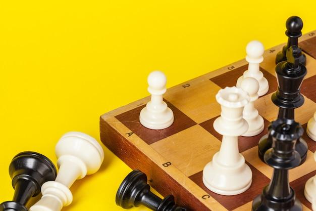 Tabuleiro de xadrez com figuras em fundo amarelo, vista superior, copie o espaço