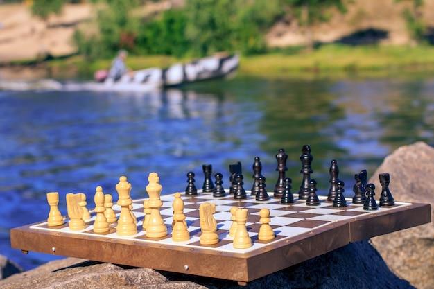 Tabuleiro de xadrez com peças de xadrez na rocha com dique do rio e lancha no fundo. foco seletivo nas peças brancas. jogo de xadrez ao ar livre