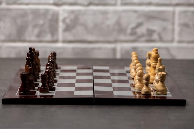 Tabuleiro de xadrez com peças espaçadas em um fundo cinza