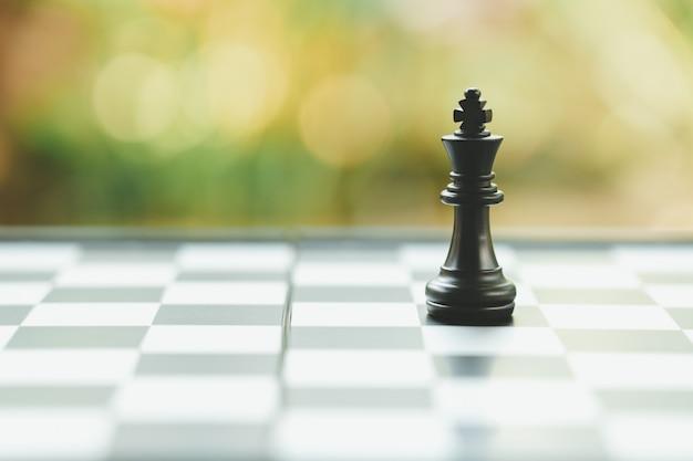 Tabuleiro de xadrez com uma peça de xadrez nas costas. negociação nos negócios. como pano de fundo