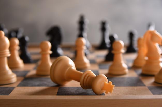 Tabuleiro de xadrez com xadrez, preto e branco em uma parede cinza