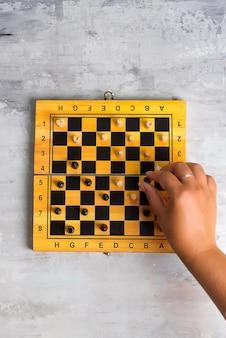 Tabuleiro de xadrez de madeira e mão de mulher fazendo movimento de xadrez
