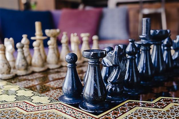 Tabuleiro de xadrez desfocado com figuras de mármore marrom e preto