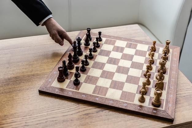 Tabuleiro de xadrez do close up com partes ajustadas primeiramente. dedo indicador masculino toque uma peça de xadrez