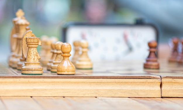Tabuleiro de xadrez do close-up com xadrez, vintage, velho, tabuleiro de xadrez de madeira. as pessoas jogam xadrez em um parque da cidade