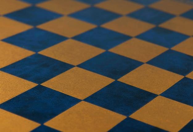 Tabuleiro de xadrez. fundo de textura quadriculada de couro de cor azul e dourado