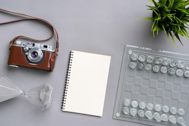 Tabuleiro de xadrez, notebook, câmera e ampulheta
