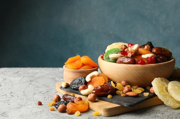 Tabuleiro e tigelas com frutas secas e nozes na mesa cinza