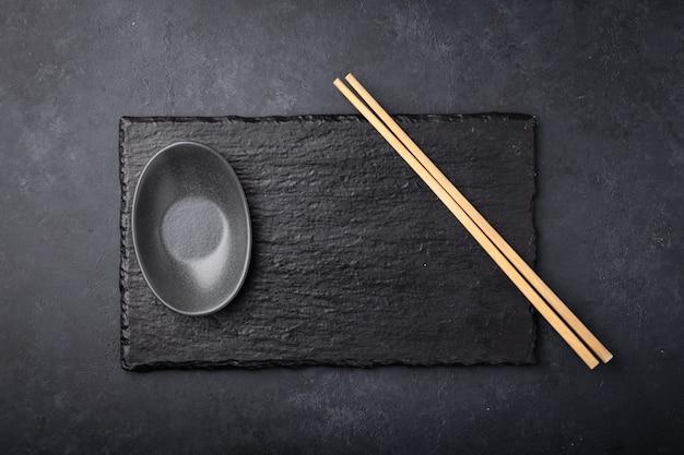 Tabuleiro vazio de sushi em um fundo preto com pauzinhos e molheira