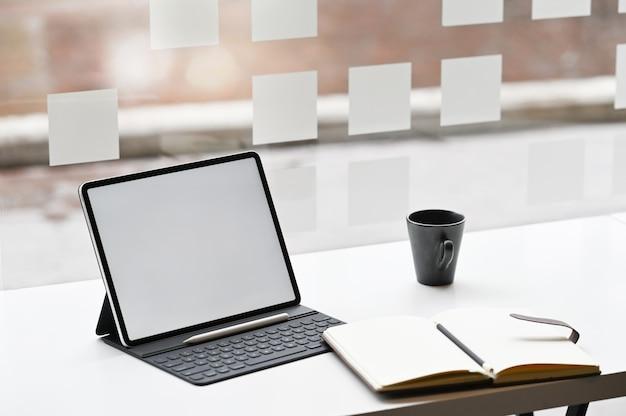 Tabuleta, caderno e café de digitas na mesa.