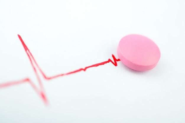 Tabuleta cor-de-rosa com a carta da cor vermelha. conceito de remédio para o coração.