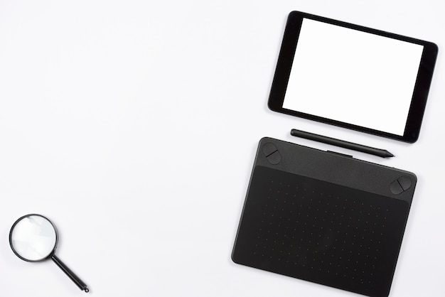 Tabuleta de digitas e tabuleta digital gráfica com estilete e lupa no fundo branco