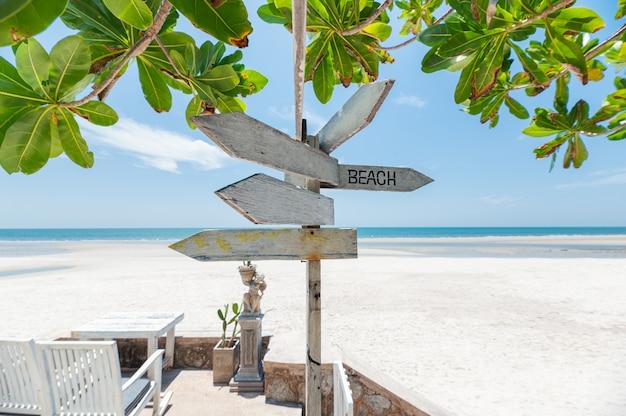 Tabuleta de madeira de setas na praia com planta verde